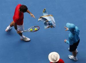Federer of Switzerland throws his towel to a ball boy after wiping his face at the Australian Open tennis tournament in Melbourne