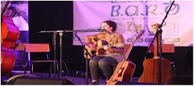 Young Begley plays guitar whilst holding a microphone stand in her mouth at last year's event.