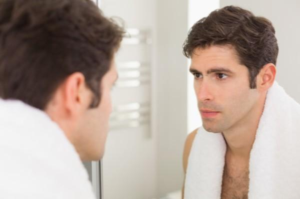 serious-young-man-looking-self-bathroom-mirror_13339-50771